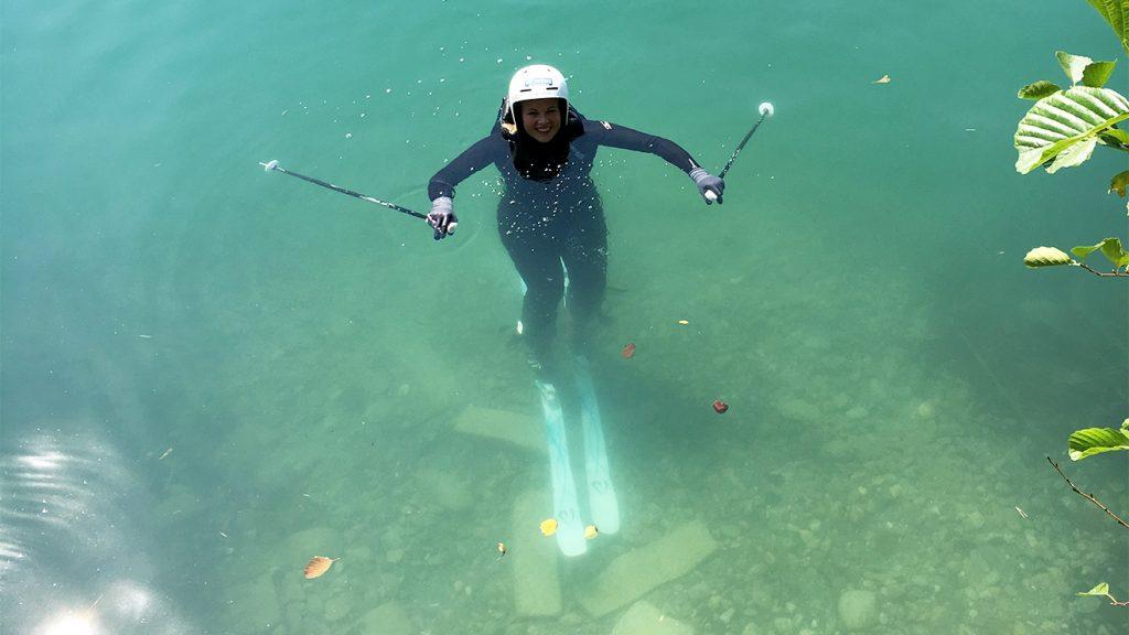 Mit Ski und Stöcken schwimmt Melanie Meilinger ans Ufer © Skiing Penguin